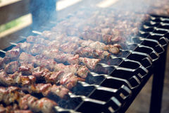 Large number of preparing kebabs on the grill Royalty Free Stock Photos