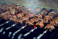 Large number of preparing kebabs on the grill Royalty Free Stock Photo