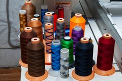 A large number of reels with colored threads in a workshop for sewing and hauling textiles for the automotive industry and. Industry stock photography