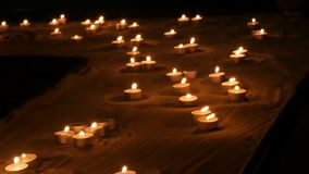A large number of small white round candles burning in the sand. Background of burning wax candles. stock video footage