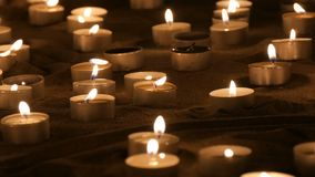 A large number of small white round candles burning in the sand. Background of burning wax candles. stock footage