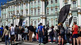 A large number of spectators at the walls of the Hermitage watch the finish of the St. Petersburg marathon on a Sunny summer day.