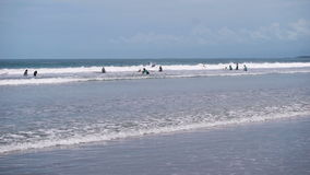 A large number of surfers trying to catch a wave off the coast. People are surfing on vacation and just swimming in the. Sea. Coastline in the surf stock footage