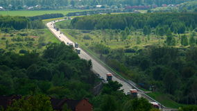 A large number of trucks and cars driving on a long road among the woods and fields. Timelapse. Highway m-7 going from Kazan stock footage