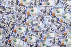 A large number of US dollar bills of a new design with a blue stripe in the middle. Top view royalty free stock images