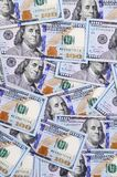 A large number of US dollar bills of a new design with a blue stripe in the middle. Top view stock photos