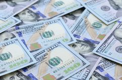 A large number of US dollar bills of a new design with a blue stripe in the middle. Top view.  royalty free stock photos