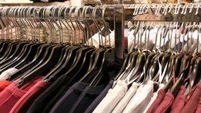 A large number of women`s clothing of different colors hangs on hangers and lies on the shelves in a clothing store of. A shopping center or mall. The problem stock video footage