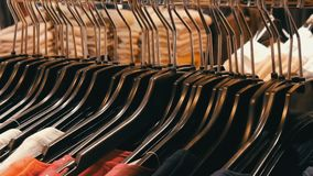 A large number of women`s clothing of different colors hangs on hangers and lies on the shelves in a clothing store of. A shopping center or mall. The problem stock footage