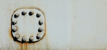 Large nuts and bolts on gray steel plate of rail bridge, lit by bright sun. Abstract industrial background, space for text on the. Right stock photography