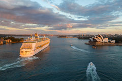 Large ocean liner unfolds in Sydney Harbour. SYDNEY - MARCH 31: Large ocean liner unfolds in Sydney Harbour. View from the Harbour Bridge at sunset. March 31 Stock Photos