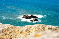 Large ocean waves lapping on the rocky island and fight for it Royalty Free Stock Image
