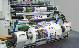 Large offset printing press or magazine running a long roll off. Paper in production line of industrial printer machine Stock Photos