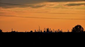 A large oil refinery in the distance. Oil and gas industrial, oil refinery plant form industry, refinery factory oil storage tank and pipeline steel with sunset stock photo
