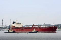 Large oil tanker with two tugs. Large oil tanker being maneouvered by two tug boats Stock Images