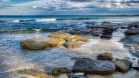 Large old aged rocks and in calm shallow sea water soft waves blue sky with clouds, wide image. Queensland Australia stock images