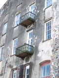 Large Old Building. Wrought iron balconies attached to an old waterfront multistory building. The blue sky is reflected in the white wooden windows Royalty Free Stock Images