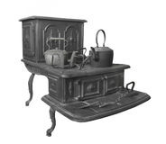 Large old cast iron stove isolated. Large old two-level black cast iron wood-burning, cooking stove with pots, kettles, and clothes irons on top.  Isolated on Royalty Free Stock Images