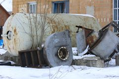 A large old dismantled and rusty tank for collecting milk. In an abandoned and destroyed factory against the wall. Destruction and vandalism. Ukraine stock image