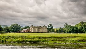 A large old farm house near a river with storm clouds royalty free stock image