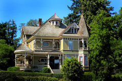 Large Old Historic Home. Frontal view of a beautiful large old luxurious  yellow country home with lots of gingerbread trim, a wide porch and round turrets Stock Images