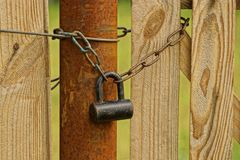 A large old padlock and chain on a pipe and a wooden board. Old padlock on chains around a rusty pipe and wooden fence boards Royalty Free Stock Images