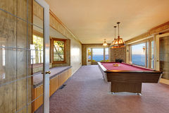 Large old room with pool table, window bench and water view. Royalty Free Stock Photography