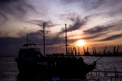 A large, old ship is at the pier at sunset. A large, old ship stands at the dock at sunset. bright beautiful sky royalty free stock photography