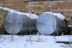A large old tank for collecting milk in an abandoned. And destroyed factory against a background of white snow in winter. Destruction and vandalism. Ukraine royalty free stock photo