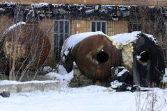 A large old tank for collecting milk in an abandoned. And destroyed factory against a background of white snow in winter. Destruction and vandalism. Ukraine stock images