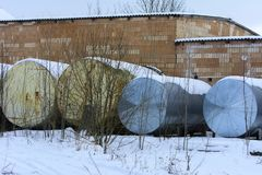 A large old tank for collecting milk in an abandoned. And destroyed factory against a background of white snow in winter. Destruction and vandalism. Ukraine stock image