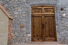 Large old wooden door in rock wall Royalty Free Stock Photo
