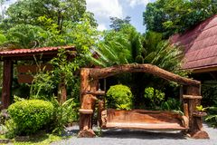 Wwooden swing bench with fountain and pond behind, jungle background, Thailand. Large old wooden swing bench surrounded by palms and plants on green tropical stock photos