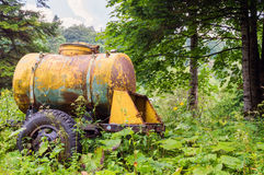 Large old yellow watering and milk barrel water tank. On wheels stay in forest among plants stock image