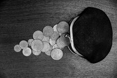 Black purse with old coins on a gray table Royalty Free Stock Image