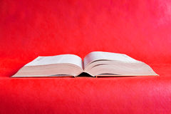 Large open book on a red  background Stock Photo
