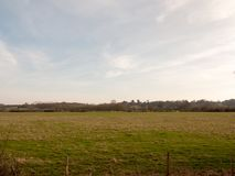 Large open grassland field farm pasture plain spring clear sky background. Essex; england; uk royalty free stock image