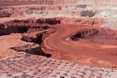 Iron ore mining. Large, open-pit iron ore mine showing the various layers of soil and iron rich ore Stock Images