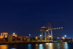 Large operating crane at harbor night time. View of Large operating crane at harbor night time Royalty Free Stock Photos