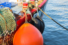 Large orange buoy on red fishing boat. Stock Images