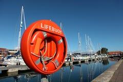 Large orange lifebuoy in Weymouth harbour stock images