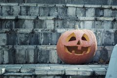 A large orange pumpkin with a carved face. The pumpkin stands on the steps in the sinister twilight. Happy Halloween stock image