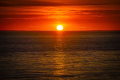 Large orange sunset above the ocean, France royalty free stock photography