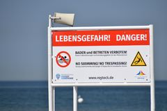 Large orange and white sign located on the beach warning of danger an advising no swimming or trespassing. Warnemunde, Germany - June 8, 2018: Large orange and royalty free stock images