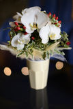 Large orchids and garden accents bridal bouquet in a white vase. The bride`s most essential detail on the big day. Bridal floral arrangement positioned on a stock photos