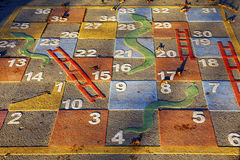 Large outdoor snakes and ladders game. In a park stock image