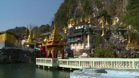 Large outdoor temple. Handheld, panning, wide shot of a Buddhist temple exhibit stock video