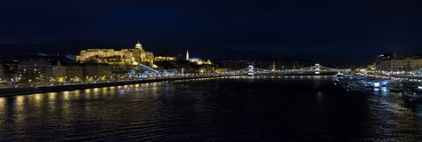 Large panoramic view of Buda Castle Royal Palace. Large panoramic view of beautiful illuminated famous Buda Castle Royal Palace building and bridge at night stock images