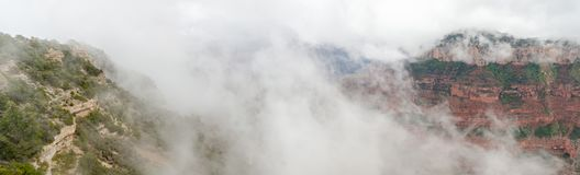 Large panoramic view on Grand Canyon under heavy fog. USA royalty free stock photography