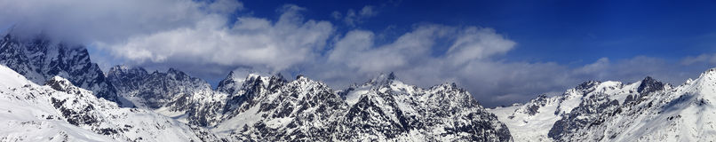 Large panoramic view on snowy mountains in haze at sunny day Stock Images